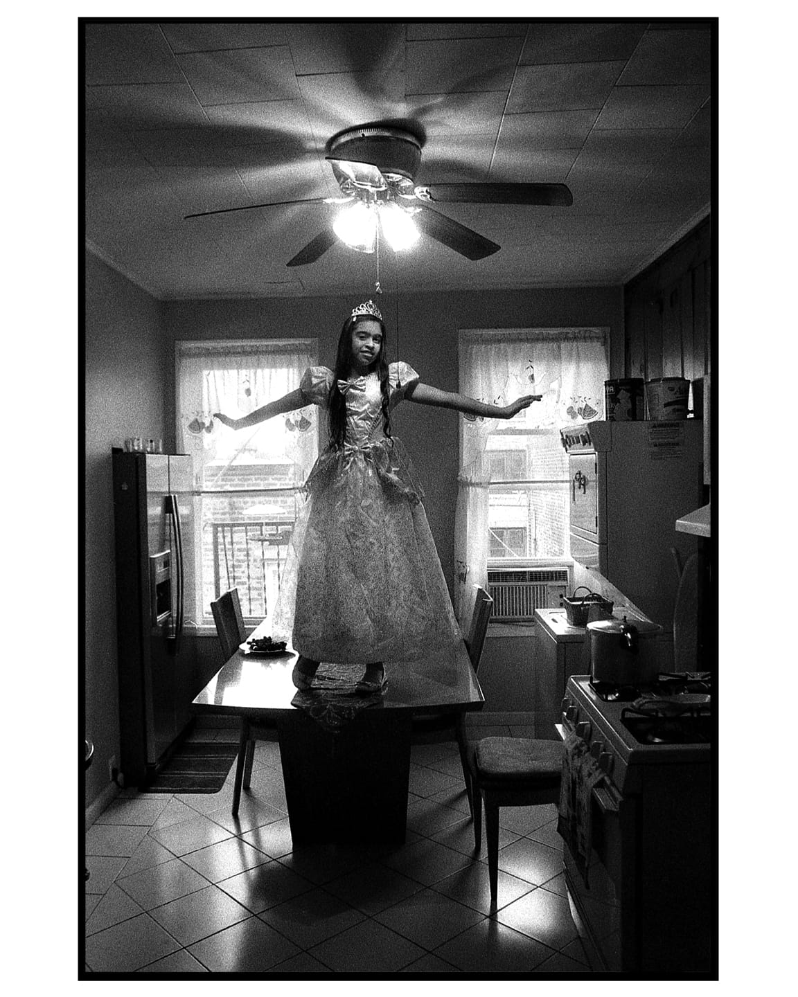 A portrait of my daughter, Alicia. She is posing on top of her grandmother's kitchen table, dressed in her Halloween costume.